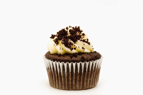 A chocolate cupcake decorated with chocolate biscuit crumbs