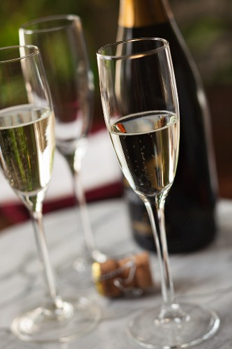 Three glasses of champagne with the cork and the bottle