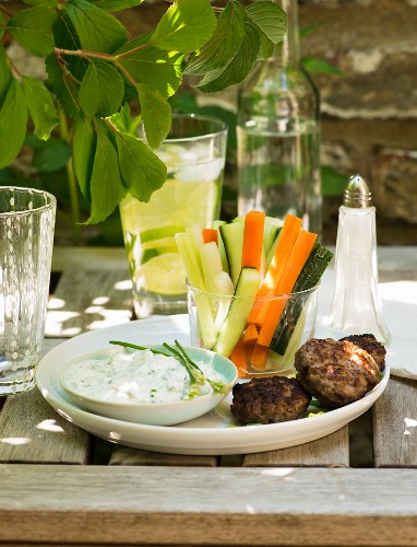 Meatballs with vegetable sticks and a dip on a garden table