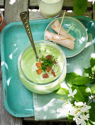 Herb soup with pesto and rolls of ham on a garden table