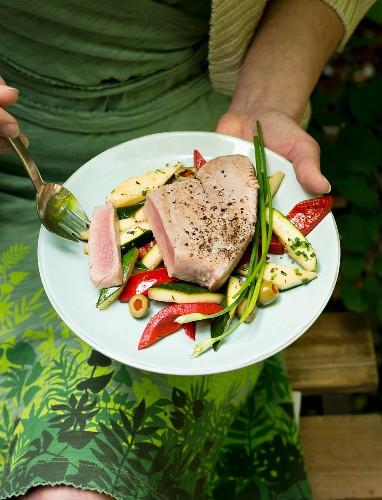 A woman eating tuna fish salad in a garden