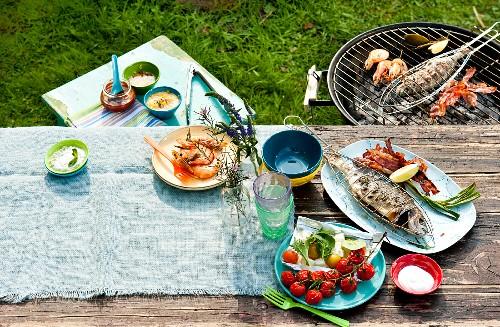 Grillen im Garten mit Grillgut auf Grill & gedecktem Gartentisch