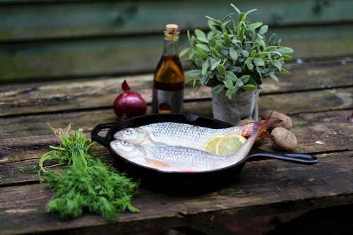 Fresh fish, herbs, vegetables and balsamic vinegar on a wooden table