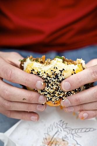 Person hält Gua Bao Burger mit Sesam (Asiatisches Street Food)