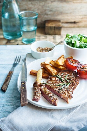 Steak with grilled tomatoes, chips and salad