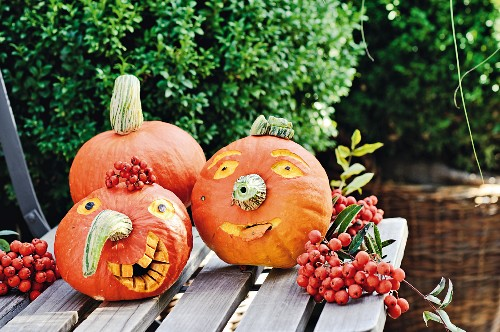 Faces carved on pumpkins on garden table