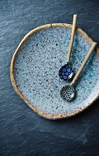 Two handcrafted ceramic spoons on a blue ceramic plate (Asia)