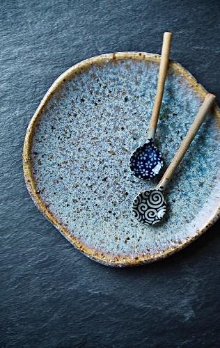 Zwei handgefertigte Keramiklöffel auf blauem Keramikteller (Asien)