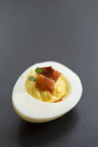 A devilled egg with bacon