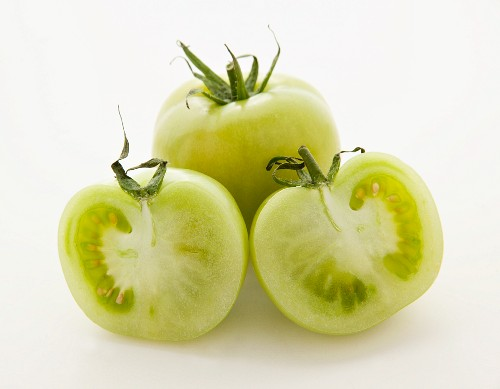 Green tomatoes, whole and halved, on white surface