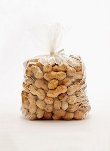 A plastic bag of peanuts against a white background