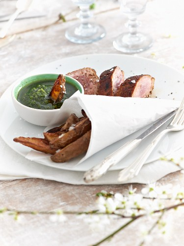 Green sauce served with pork fillet and potato wedges