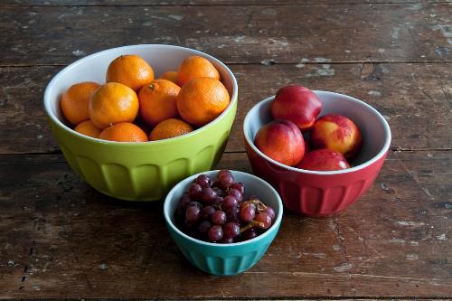 Mandarins, nectarines and grapes in ceramic bowls