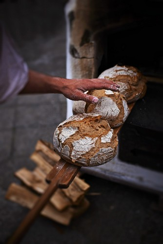 A baker removing a freshly baked loaf of bread from the oven