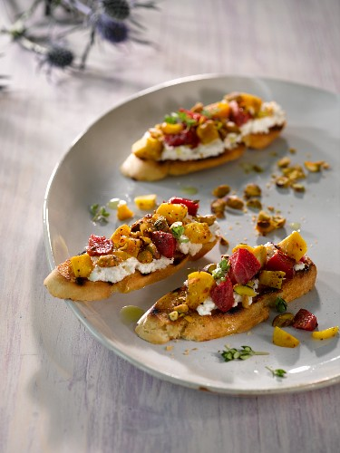 Crostini topped with golden beets and beetroots, cottage cheese and pistachio nuts