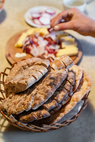 Homemade bread (crispy unleavened bread from South Tyrol) with bacon and cheese