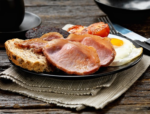 An English breakfast with bacon, fried eggs, tomatoes and black pudding