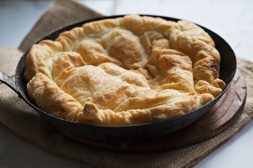 Tarte Tatin zubereiten: Fertig gebackener Teig auf karamelisierten Äpfeln