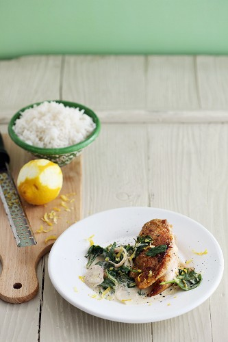 Fried chicken breast fillet with lemon zest and spinach
