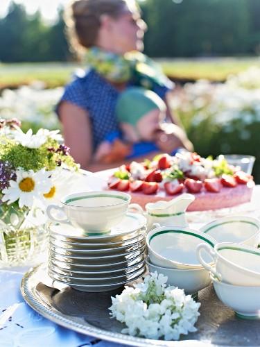Erdbeertorte und Teetassen auf Gartentisch