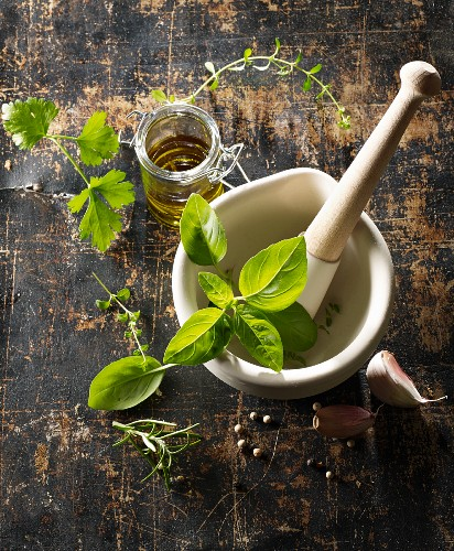 Various fresh herbs and olive oil in a mortar