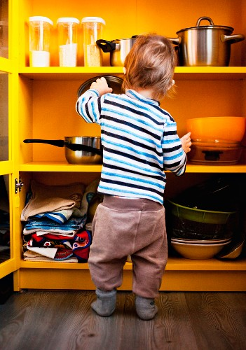A little boy in front of a kitchen cupboard