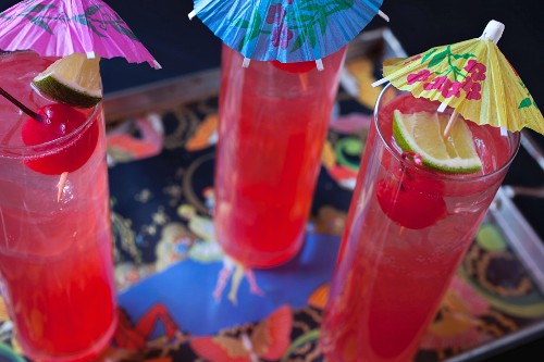 Three Singapore Slings with paper umbrellas on a tray