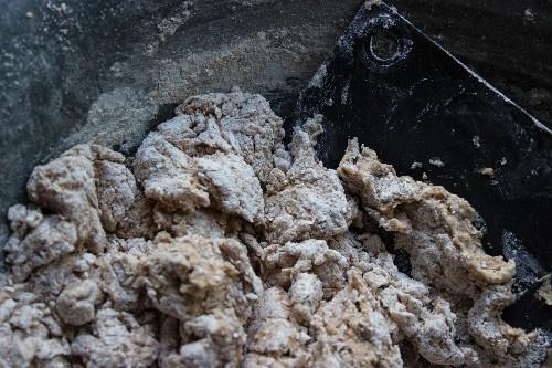 Raw spelt dough in an enamel bowl with a dough card and flour