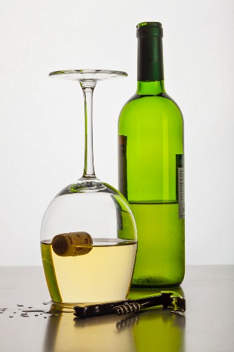 A cork floating inside an upside-down glass of wine