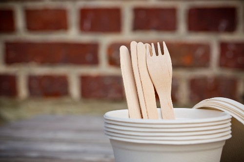 A stack of take-away cups with wooden forks