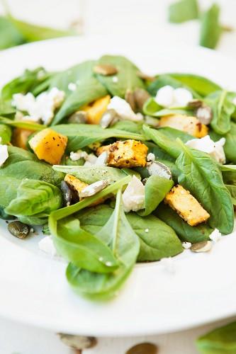 Spinach salad with pumpkin, feta cheese and pumpkin seeds