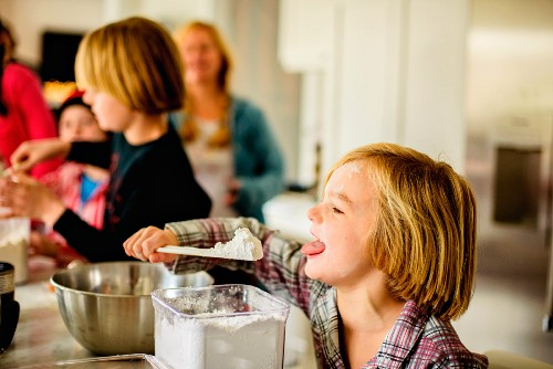 A boy eating icing sugar from a spatula in a kitchen
