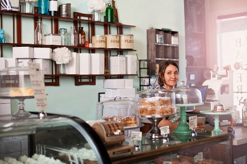 A woman standing behind the counter of a vegan bakery