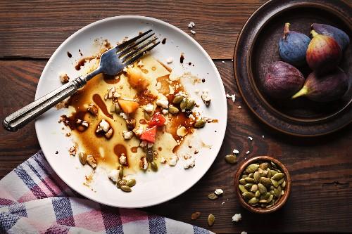 Essensreste von Kopfsalat mit Feigen, Zuckerschoten, Melonen und Kürbiskernen