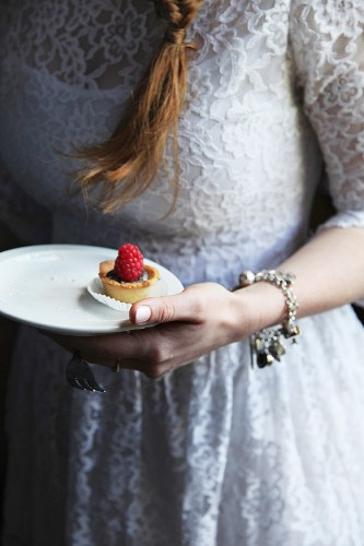 A bride holding a mini chocolate and raspberry tartlet on a plate
