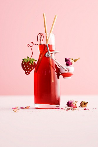 A bottle of homemade strawberry and rose syrup