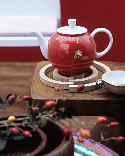 Red teapot on spiral birchwood trivet