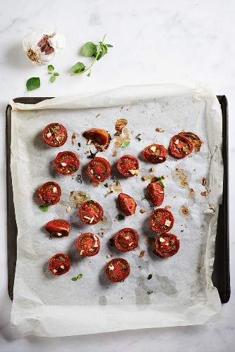 Oven-roasted zebra tomatoes on a baking tray lined with baking paper (seen from above)