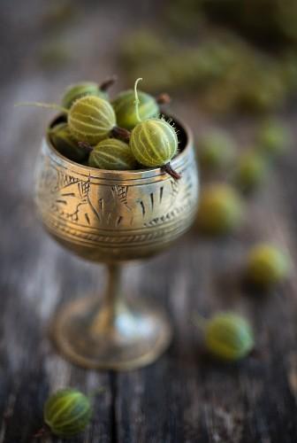 Grüne Stachelbeeren in antikem silbernem Kelch