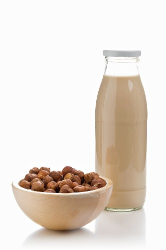 A bottle of hazelnut milk and a bowl of hazelnuts