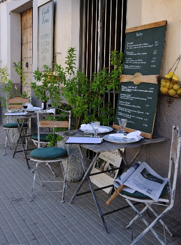 Bistro tables laid outside a cafe