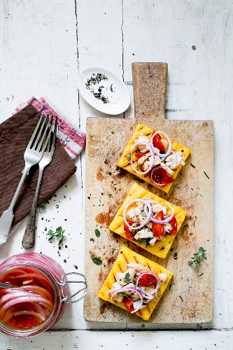 Polenta crostini with pickled red onions and fish