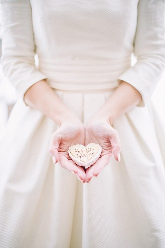 Bride holding heart-shaped wedding pastry