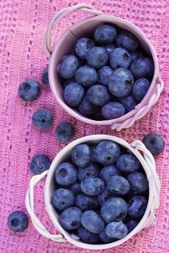 Fresh blueberries in pink pots on a homemade, crocheted table mat