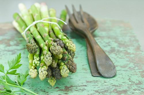A bunch of green asparagus and parsley on a rustic wooden table with salad servers