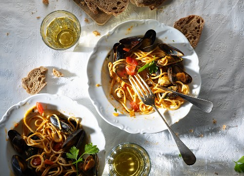 Spaghetti with mussels, white wine and bread (seen from above)