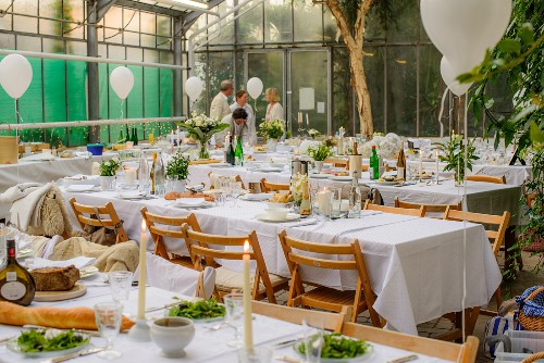 Tables set for summer party in greenhouse