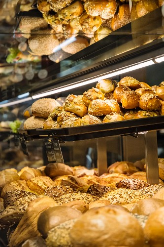 Various types of bread on shelves in a sales cabinet in the bakery