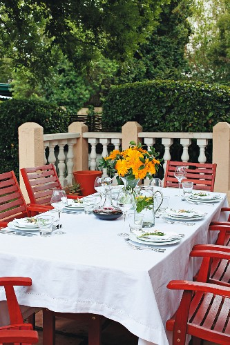 A table laid on a terrace with a white cloth, a bunch of orange flowers and carafes of water and wine