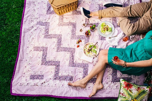 A couple sitting on a patchwork blanket with glasses of red wine and a picnic basket
